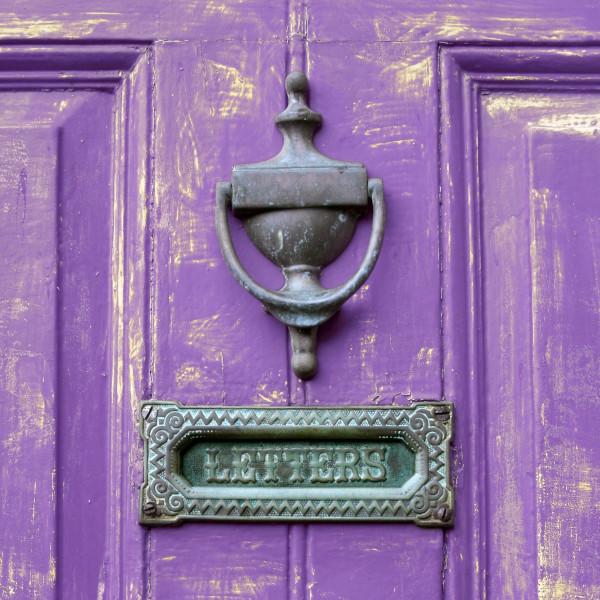 A letterbox in a purple door